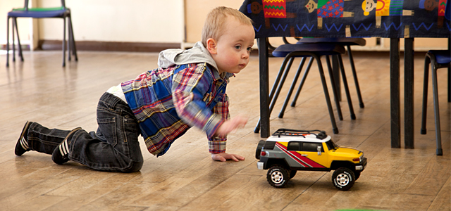 Boy playing on the floor with a truck