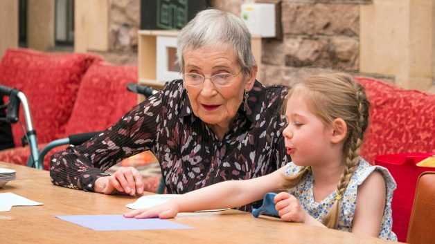 Child helping pensioner at old peoples home