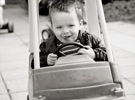 Boy riding in a toy car