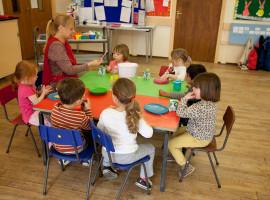 Pre-school worker helping kids