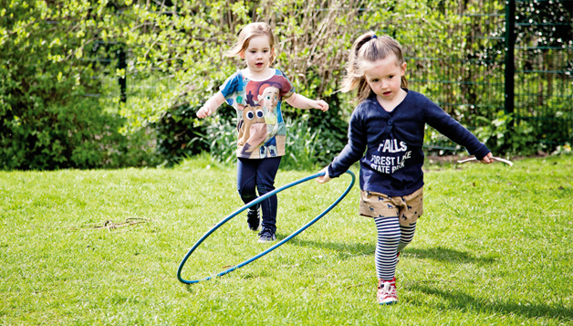 Children playing in a field with hula hoops