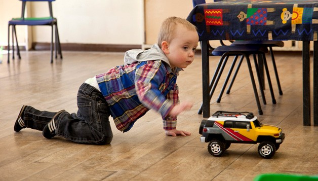 Little boy playing with a truck at pre-school